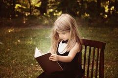 Умная книга образования чтения ребенка снаружи Стоковое Изображение