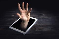 Умная концепция наркомании телефона на красной предпосылке рука тонет в экране Стоковое Изображение