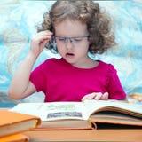 Умная маленькая девочка с стеклами читая книгу стоковые изображения