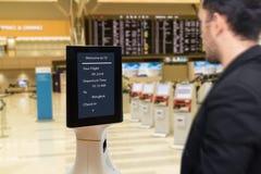 Умная робототехническая концепция технологии, пассажир следовать роботом обслуживания к встречному проверяет внутри в авиапорте,  стоковое изображение