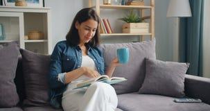 Умная чашка чаю удерживания книги чтения молодой дамы сидя на кресле в квартире акции видеоматериалы