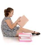 Умная школьница девушки читая книгу сидя дальше Стоковые Фотографии RF