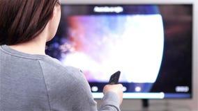 Умное ТВ и женщина отжимая дистанционное управление акции видеоматериалы