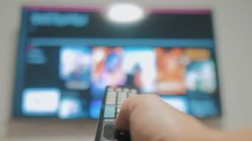 Умное ТВ с apps и рукой Мужская рука держа дистанционное управление поворачивает умное ТВ рука человека контролирует удерживание  сток-видео