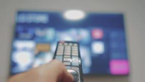 Умное ТВ с apps и рукой Мужская рука держа дистанционное управление поворачивает умное ТВ рука человека контролирует удерживание  видеоматериал