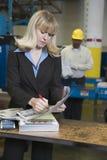 Умно одетая женщина с работником позади стоковые фотографии rf