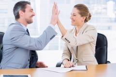 Умно одетые коллеги давая максимум 5 в деловой встрече Стоковые Фотографии RF