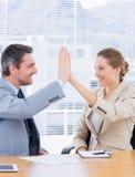 Умно одетые коллеги давая максимум 5 в деловой встрече Стоковая Фотография RF