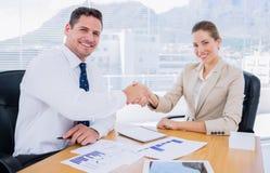 Умно одетые коллеги тряся руки в деловой встрече Стоковое Фото