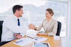 Умно одетые коллеги тряся руки в деловой встрече Стоковые Фотографии RF
