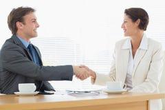 Умно одетые пары тряся руки в деловой встрече Стоковое Изображение