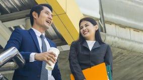 Умные азиатские бизнесмены беседа и утеха работника человека и женщины к Стоковые Фотографии RF