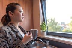 Умные азиатские женщины в кухне Стоковые Изображения