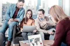 Умные и стильные работники сидя совместно и используя компьтер-книжки Стоковая Фотография RF