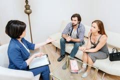Умные и тщательные люди смотрят терапевта и слушают к ей очень тщательному Профессионал объясняет к им стоковая фотография rf