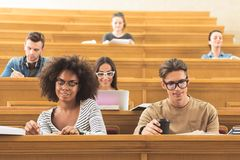 Умные студенты подготавливая для семинара в университете стоковые фото