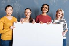 Умные счастливые женщины стоя против голубой стены стоковая фотография rf