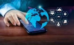 Умные телефоны и бизнесмены интернета мира связи соединений глобуса неупотребительные отжимают телефон для того чтобы связывать в стоковое изображение
