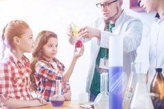 Умные школьницы участвуя в уроке химии практически Стоковое Изображение RF