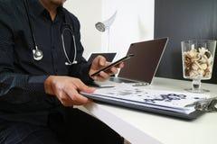 умный врач работая с умным телефоном и цифровой таблеткой Стоковое Фото