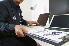 умный врач работая с умным телефоном и цифровой таблеткой Стоковые Фотографии RF