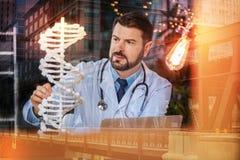 Умный генетик получая идею пока смотрящ модель дна Стоковые Изображения
