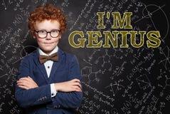 Умный гений ребенк на предпосылке доски с формулой науки и математик стоковые изображения