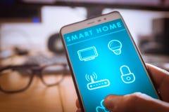 Умный домашний интерфейс технологии на экране приложения смартфона, удерживающем приспособлении человека стоковое изображение