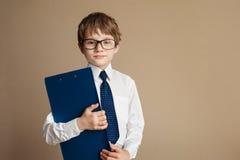 Умный мальчик в элегантном костюме и стекла сидя на софе Chesterfield с бумагой таблетки принципиальная схема воспитательная Дети стоковое фото rf
