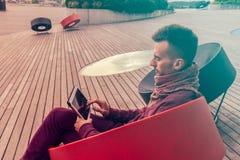 Умный молодой человек работает на планшете outdoors в городском общественном месте стоковые фотографии rf