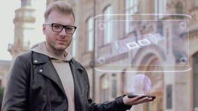 Умный молодой человек со стеклами показывает схематический привод USB hologram видеоматериал