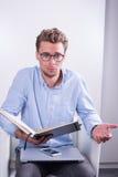 Умный молодой профессионал с открытой тетрадью в его руках стоковые изображения rf