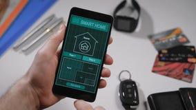 Умный дом, применение на телефоне Человек управляет различными параметрами его дома от smartphone домашнее франтовское видеоматериал