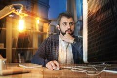 Умный работник думая пока смотрящ экран его компьютера Стоковое Изображение