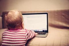 Умный ребенок работая на портативном компьютере Стоковые Изображения RF