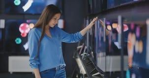 Умный современный женский клиент выбирая большие телевизоры в магазине электроники Новые поколения экрана сток-видео