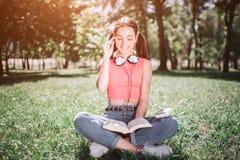 Умный студент сидит на траве в парке и читает книгу Она сидит при ее пересеченные ноги Девушка держит одно стоковая фотография rf