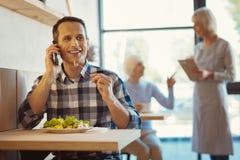 Умный счастливый человек наслаждаясь его едой Стоковое Изображение