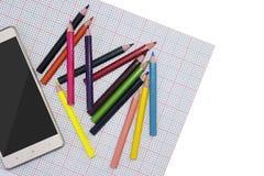 Умный телефон и покрашенные карандаши на светлом взгляде со стороны предпосылки насмешка вверх по образцу стоковая фотография rf
