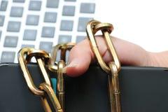 Умный телефон связан к руке ` s человека крепкой цепью стоковые фото