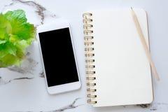 Умный телефон с пустым экраном на пустой предпосылке бумаги тетради Стоковая Фотография RF