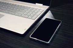 Умный телефон с экраном и ноутбуком космоса экземпляра на предпосылке деревянного стола Пустой черный экран мобильной левой сторо стоковые изображения