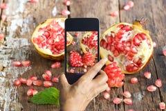 Умный телефон принимает фото гранатового дерева на деревянной предпосылке Стоковые Изображения RF