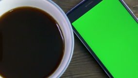 Умный телефон с зеленым экраном рядом с кофейной чашкой видеоматериал