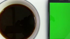 Умный телефон с зеленым экраном рядом с кофейной чашкой сток-видео