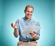 Умный усмехаясь студент при отличная идея держа листы бумаги Стоковые Фото