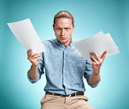 Умный усмехаясь студент при отличная идея держа листы бумаги Стоковое Фото