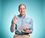Умный усмехаясь студент при отличная идея держа листы бумаги Стоковое Изображение RF
