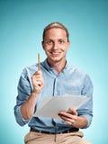 Умный усмехаясь студент при отличная идея держа листы бумаги Стоковое Изображение