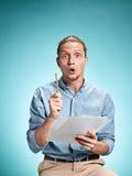 Умный удивленный студент при отличная идея держа листы бумаги Стоковая Фотография RF